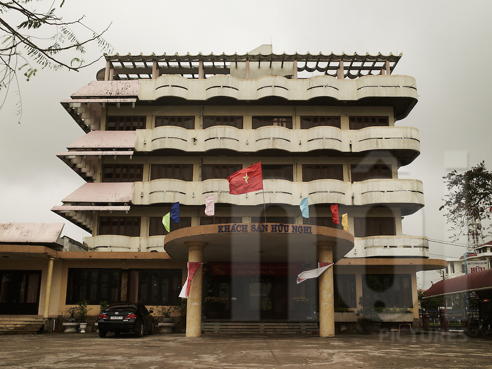 Frontage of an hotel owned by government, controled by committee. Vietnamese flag hung on the frontage of the hotel. Quang binh province , Viet Nam. Asia.