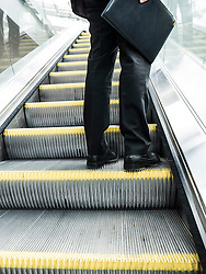Businessman on Escalator Holding Leather Case
