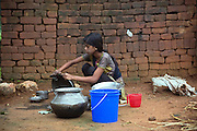 Tabasum Khatun, 14, is washing dishes in the courtyard of her home in Algunda village, pop. 1000, Giridih District, rural Jharkhand, India.