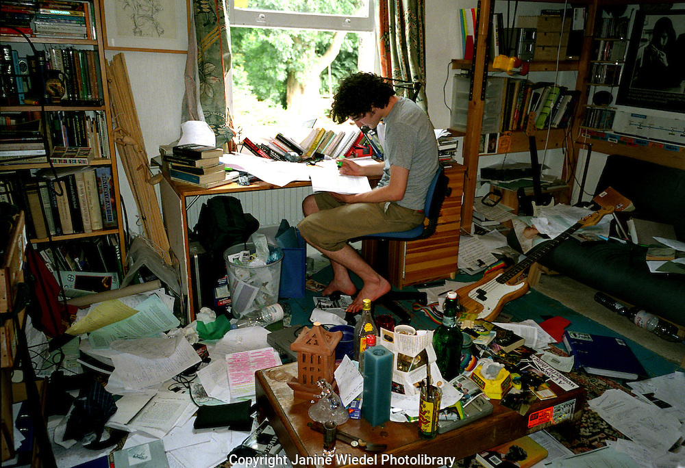 Teenage boy studying in his very messy bedroom.