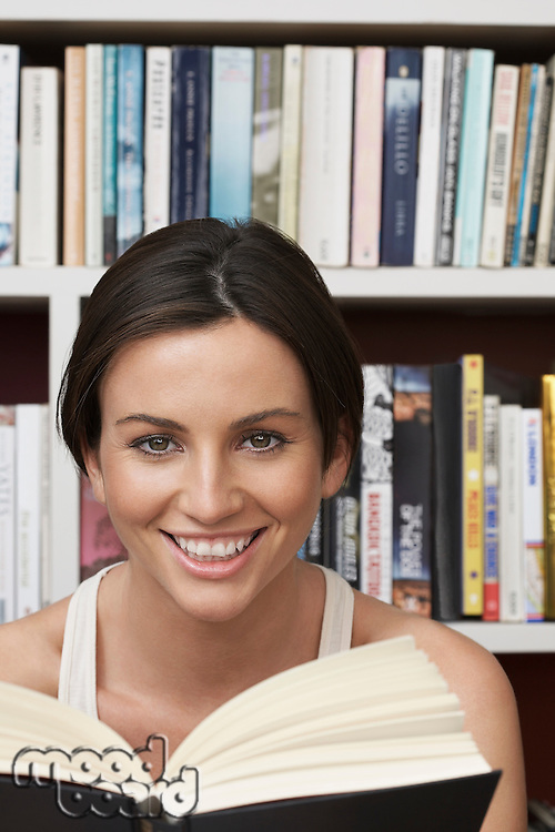 Young woman holding book by bookshelf portrait