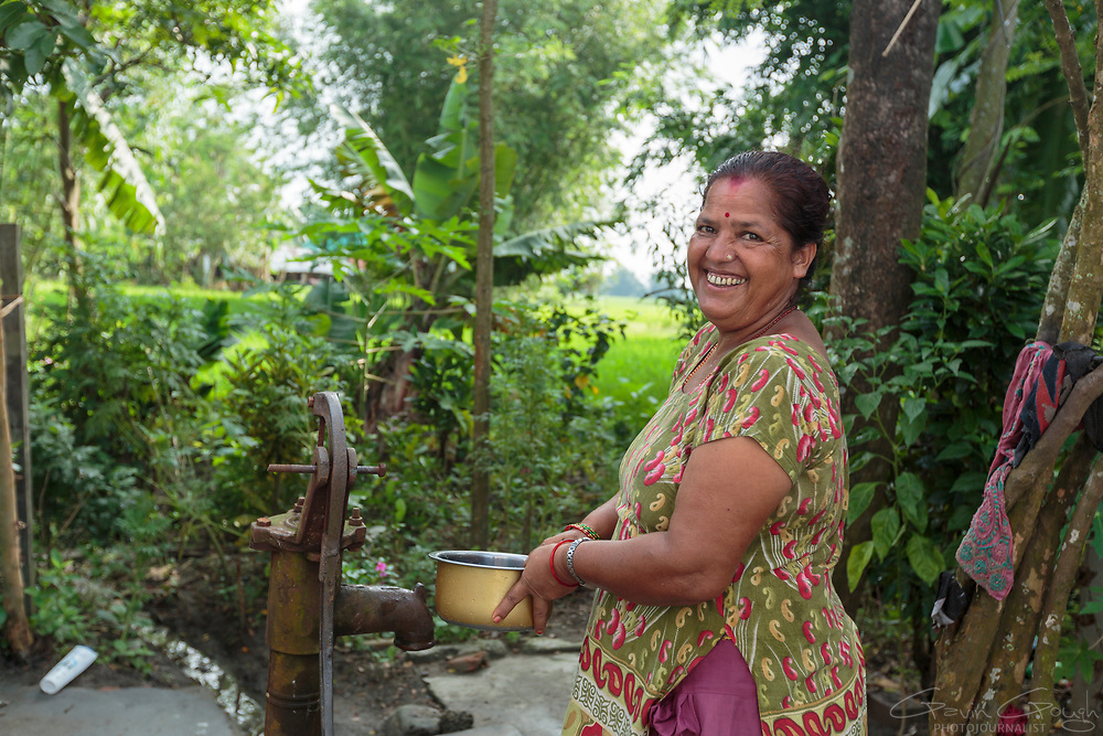 Ever smiling, Parbati collects water for her biosand filter from a communal hand pump.