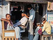 Man having his hair cut at hairdresser in Bundi (India)