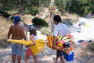 People carrying beach paraphenalia walking to the beach near Lakka, Paxos, Ionian Islands, Greece