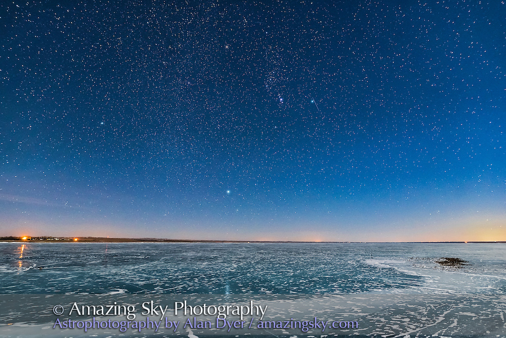 Orion and the Dog Stars (Procyon and Sirius) rising over frozen Lake MacGregor in southern Alberta, on February 2, 2017, on a clear moonlit night, with a 6-day Moon lighting the scene. Note the glitter path reflection of Sirius in the ice. The last of the evening twilight lights the horizon at right. <br /> <br /> This is with the Sigma 20mm Art lens and Nikon D750.