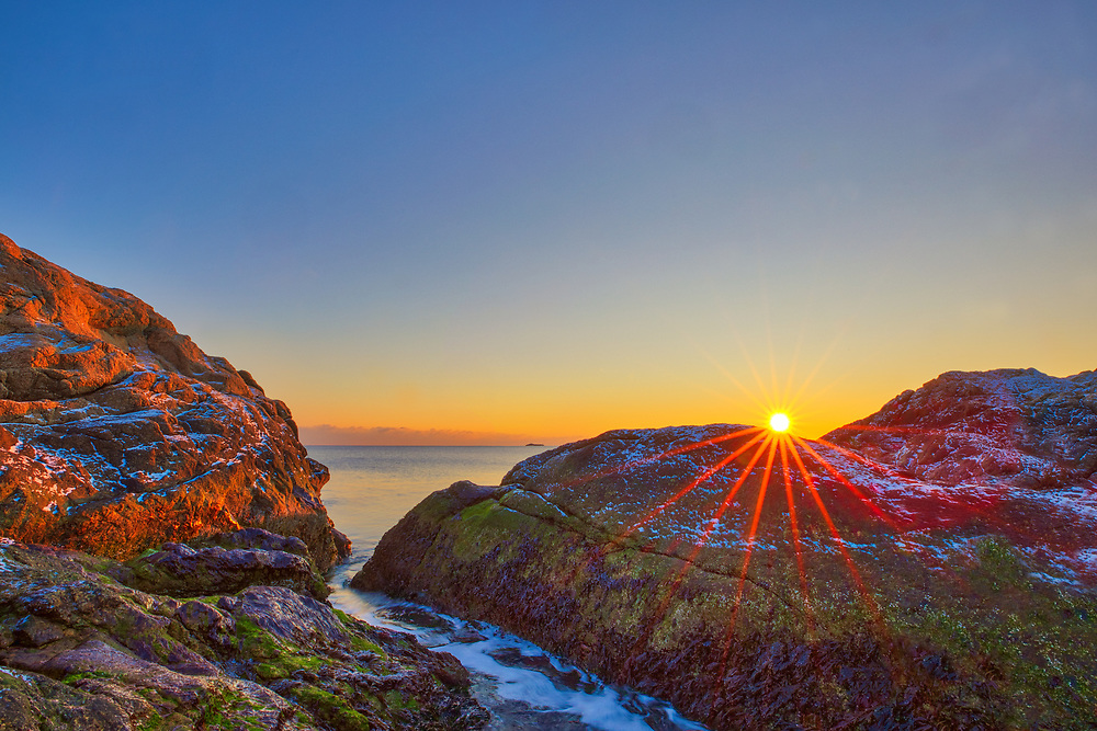 Sunrise seaview photography image in Scituate, MA. A dusting on the rocks provided a nice contrast against the rising sun. It was cold but the solitude at this location made it a worthwhile experience.<br />