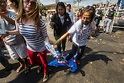 "01 FEBRUARY 2014 - BANGKOK, THAILAND: Thai voters stomp on a PRDC banner during a march to a polling place to vote. The voters were turned back by police who blocked access to the polls because armed anti-government protestors would not allow voters to cast their ballots. Thais went to the polls in a ""snap election"" Sunday called in December after Prime Minister Yingluck Shinawatra dissolved the parliament in the face of large anti-government protests in Bangkok. The anti-government opposition, led by the People's Democratic Reform Committee (PDRC), called for a boycott of the election and threatened to disrupt voting. Many polling places in Bangkok were closed by protestors who blocked access to the polls or distribution of ballots. The result of the election are likely to be contested in the Thai Constitutional Court and may be invalidated because there won't be quorum in the Thai parliament.    PHOTO BY JACK KURTZ"
