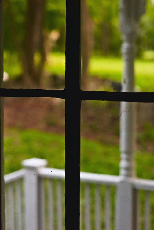 White porch railing, green lawn, trees through door window