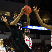 15 March 2018: San Diego State Aztecs guard Jeremy Hemsley (42) goes up for an off balanced shot while being defended by Houston Cougars forward Nura Zanna (13) and guard Armoni Brooks (3) in the first half. The San Diego State Aztecs got knocked out in the first round by Houston on a last second layup to lose 67-65  at Intrust Bank Arena in Wichita, Kansas.