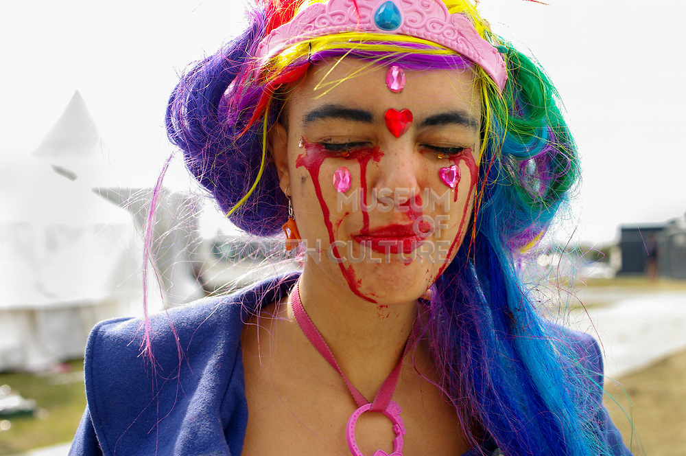 A portrait of a girl with a colourful wig, faceprint and jewels, Boomtown, Matterley Estate, Alresford Road, near Winchester, Hampshire, UK, August, 2010