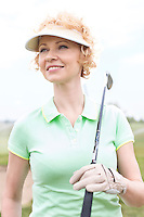 Thoughtful middle-aged woman looking away while holding golf club