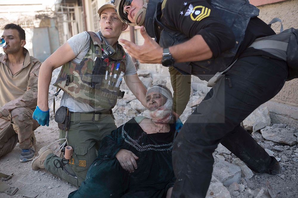 © Licensed to London News Pictures. 15/06/2017. Mosul, Iraq. A volunteer medic, working with the Iraqi Army, tends to an injured elderly Mosul resident, recently escaped from Islamic State territory, as troops prepare to evacuate her in an armoured Humvee.<br /> <br /> Despite heavy fighting between the Islamic State and Iraqi Security Forces many civilians have started to leave ISIS territory in West Mosul. Mosul residents, many of whom have been in hiding in their homes since the start of the West Mosul Offensive, often have to run through ISIS sniper and machine gun fire to reach the safety of Iraqi Security Forces positions. Photo credit: Matt Cetti-Roberts/LNP