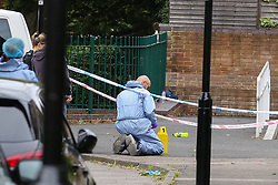 © Licensed to London News Pictures. 04/07/2020. London, UK. A forensic officer places an evidence marker on Roman Way, Islington in north London as police launch a murder investigation following fatal shooting. Police were called at at 3.20pm to Roman Way, following reports of shots fired.  Officers attended with LAS and found a man, believed to be aged in his early 20s, suffering from gunshot injuries. Despite their best efforts, he was pronounced dead at the scene. Photo credit: Dinendra Haria/LNP