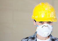 Portrait of female worker wearing dust mask and hardhat over colored background