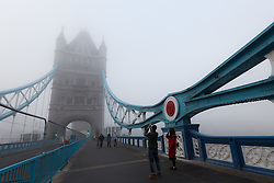 © Licensed to London News Pictures. 17/12/2016. LONDON, UK.  Tourists take photographs on Tower Bridge during foggy weather this morning. London and the River Thames was shrouded in thick fog this morning.  Photo credit: Vickie Flores/LNP