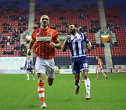 Blackpool Defender Tom Aldred and Wigan Striker Craig Davies chase the ball during the Sky Bet League 1 match between Wigan Athletic and Blackpool at the DW Stadium, Wigan, England on 12 December 2015. Photo by Pete Burns.