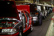A car worker fits engines on the production line in the German BMW-owned Rover factory in Cowley, Solihull, England. New vehicles come off the line at a constant rate for sale in the domestic British and export markets. Motor car production has taken place at Cowley near the city of Oxford, England for over ninety years. The car factory is known today as Plant Oxford and is now owned by BMW and has been extensively redeveloped. It remains the largest industrial employer in Oxfordshire employing more than 4,300 people.