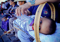 Eight-month-old Marshall Stoney of Glendale, Arizona lies in a traditional cradle board and receives a bottle before his nap.  He attended the All-around Championships in Holbrook, Arizona with his mother and brother.  From spring through fall there is a rodeo somewhere on the Navajo Nation almost every weekend.  Most of the rodeos are sponsored by one of several Navajo groups.  The largest, with about 400 members, is the forty-year-old All Indian Professional Rodeo Cowboy Association.