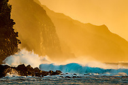 Ocean waves roll in and crash against cliffs on the rugged Na Pali Coast, with the light of the setting sun, Kauai, Hawaii,. © 2010 David A. Ponton
