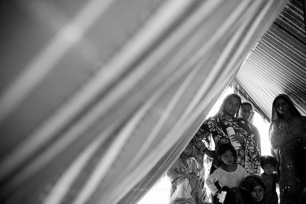 Young expecting mothers gather in a tent to get an antinatal check-up with one of the visiting doctors that provide maternal care in a tent camp for the IDP's (Internaly displaced people) established after the floods. Karachi, Pakistan, 2010