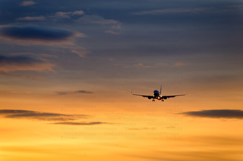 Jet airplane in flight at sunset.