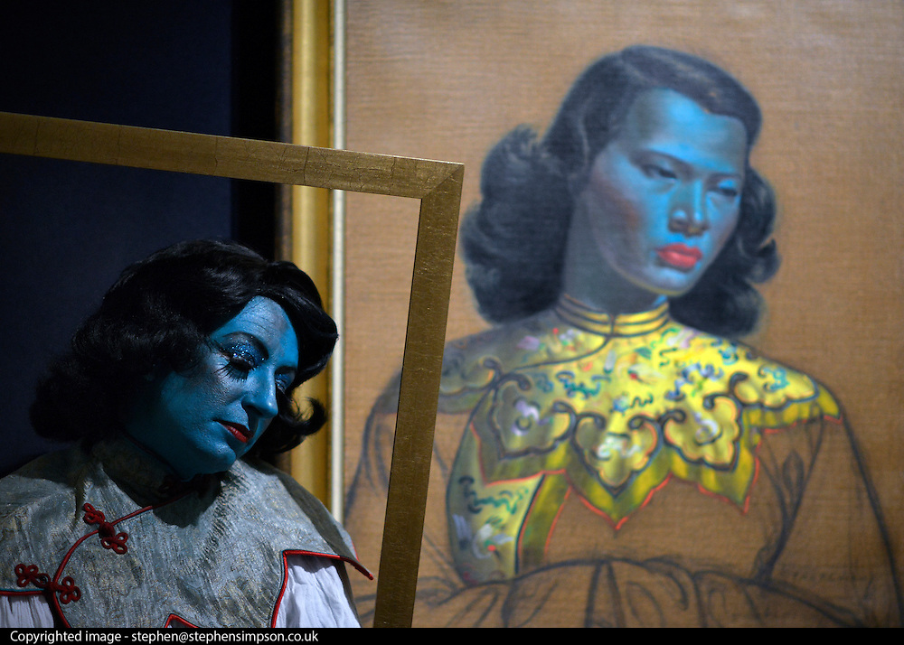 """© Licensed to London News Pictures. 18/03/2013. London, UK Caberet singer Tricity Vogue, whose successful Edinburgh Fringe Theatre Festival performances were inspired by 'Chinese Girl' poses with the original painting. Press call before the auction of """"Chinese Girl"""" by Vladimir Tretchikoff at Bonhams in London today 18th March 2013. The painting is said to be the most widely reproduced and recognisable painting in the world because of its wide reproduction in 1950's art prints. It is expected to fetch 300,000-500,000 GBP at auction on the 20th March. Photo credit : Stephen Simpson/LNP"""