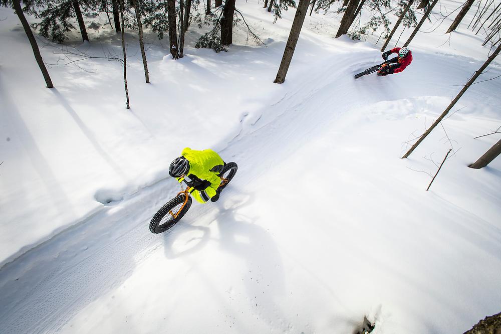 Winter cyclists on fat bikes ride the Noquemanon Trails Networks Snow Bike Route a groomed winter biking trail in Marquette, Michigan.