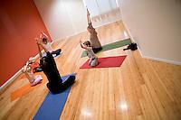 """8 Novembre, 2008. Brooklyn, New York.<br /> <br /> Due mamme con i relativi figli seguono un corso di yoga per famiglie con l'istruttrice Ute Kirchgaessner (in nero) al Bend & Bloom Yoga a Park Slope, Brooklyn, NY. Park Slope, spesso definito dai newyorkesi come """"The Slope"""", è un quartiere nella zona ovest di Brooklyn, New York, e confinante con Prospect Park.  Park Slope è un quartiere benestante che ha il maggior numero di nascite, la qualità della vita più alta e principalmente abitato da una classe media di razza bianca. Per questi motivi molte giovani coppie e famiglie decidono di trasferirsi dalle altre municipalità di New York a Park Slope. Dal punto di vista architettonico, il quartiere è caratterizzato dai brownstones, un tipo di costruzione molto frequente a New York, e da Prospect Park.<br /> <br /> ©2008 Gianni Cipriano for The New York Times<br /> cell. +1 646 465 2168 (USA)<br /> cell. +1 328 567 7923 (Italy)<br /> gianni@giannicipriano.com<br /> www.giannicipriano.com"""