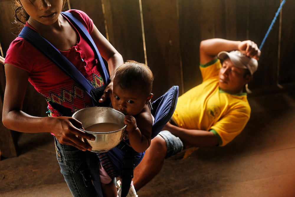 """A girl feeds a baby chica de yuca, a drink made of fermented yuca in San Pedro Sumino in August of 2009.  The """"chicha,"""" a beverage made out of yuca and offered at all times of the day.  To not accept it when offered is an insult to Kichwas.  When you first enter their house, chicha is like a strong handshake.  It  is a covenant, allowing  strangers to build a trusting friendship."""