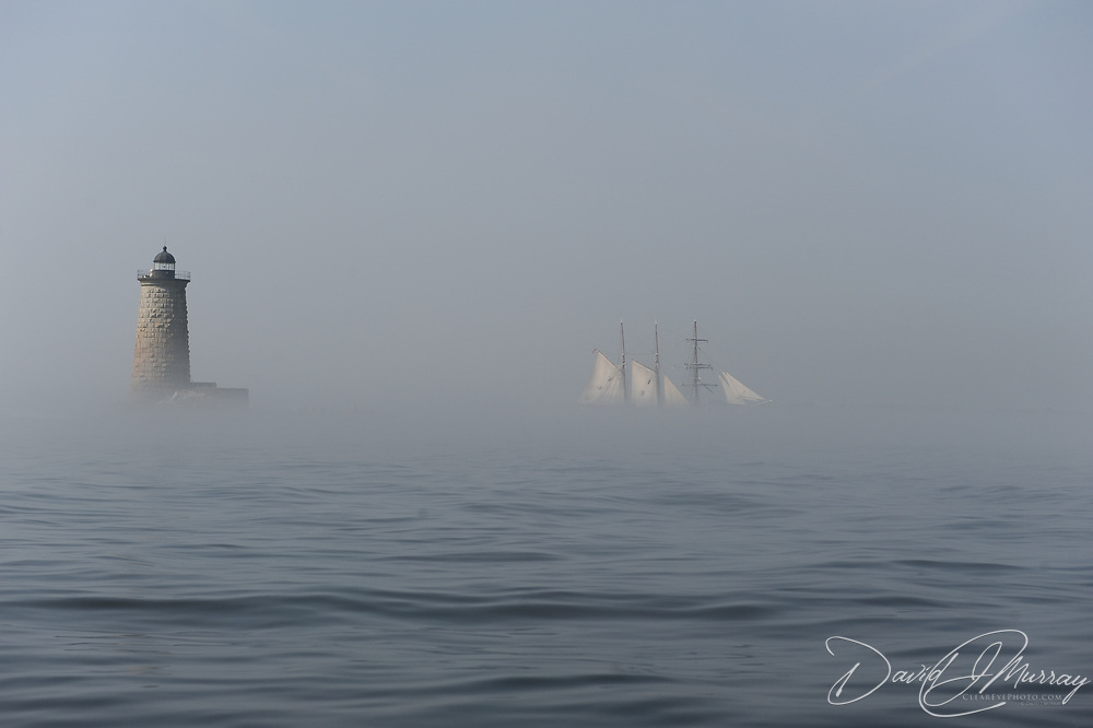 Tall ship Gazela emerges from the fog as it passes Whaleback Lightohouse in mouth of  the Piscataqua River, entrance to Portsmouth Harbor