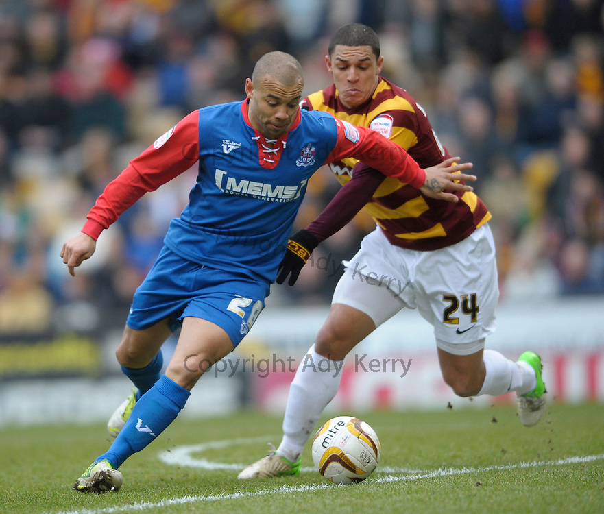 Gillingham's Deon Burton holds off a challenge from Bradford's Nathan Doyle during their npower League 2 game at the Coral Windows Stadium, Bradford, west Yorkshire, 9th February 2013.