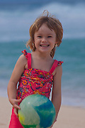 A little girl with a beach ball on the north shore of Oahu, Hawaii