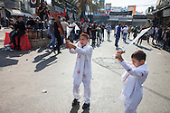 Young shiite muslim boys, with self-inflicted head wounds and traditional swords, on the streets of Nabatiye, Lebanon, commemorating the Day of Ashura.(November 14, 2013).
