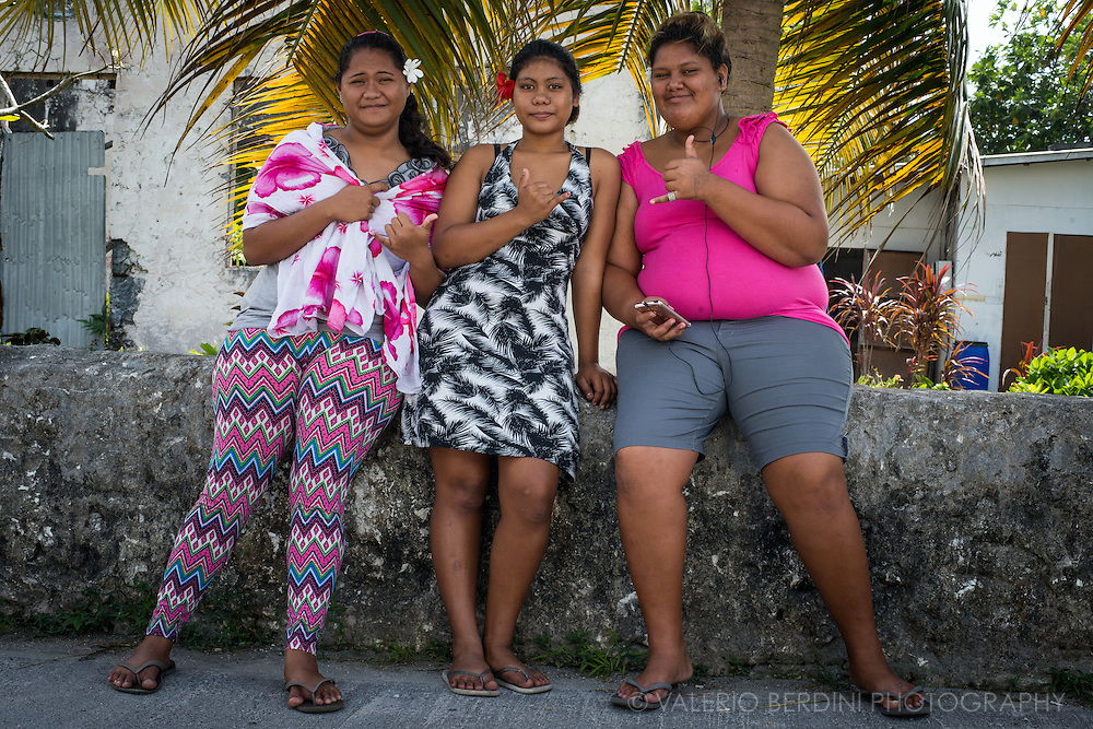 Teenagers on a sunday morning after the weekly mass gather to chat before their traditional big lunch. Life in a remote atoll in the middle of pacific can be a boring experience of isolation and loneliness. Lack of opportunities and scarcity of people developed an addiction to food and drinking boosting a serious problem of Polynesian in dealing with a widespread of obesity.