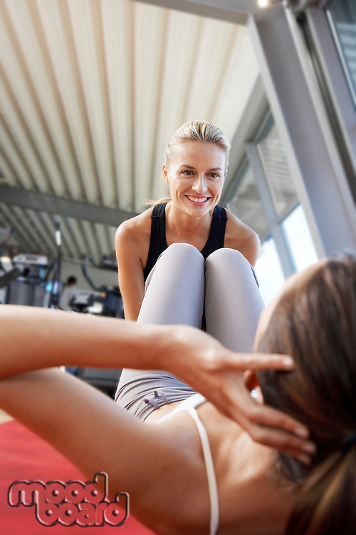 Woman holding legs of woman doing sit ups in health club