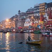 Morning rituals being performed on the banks of the holy Ganges River in Varanasi, India, at dawn.