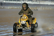 a competitor wearing a fancy dress costume takes part on a Quad bike at the Weston Beach Race in Somerset.