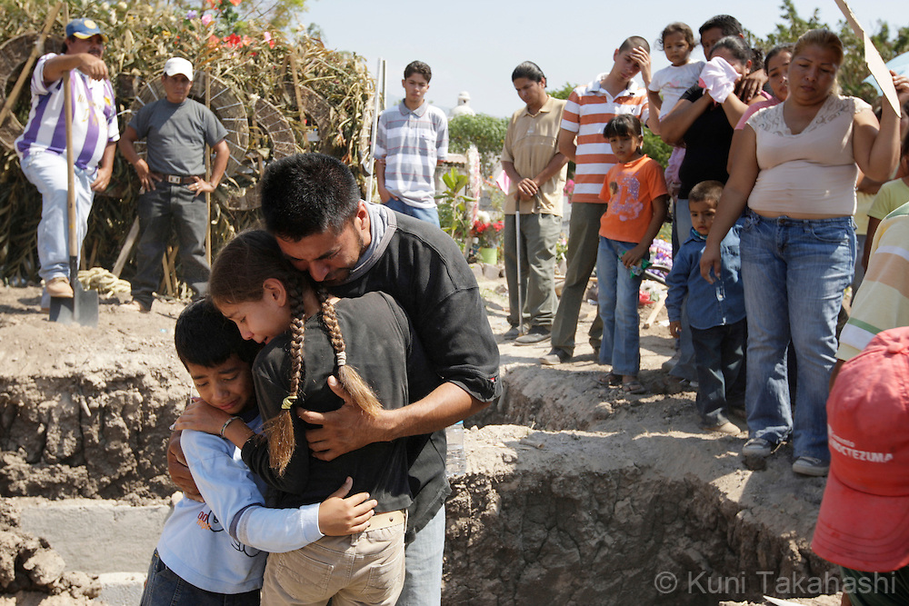 Family members of Mariana de la Torre, from left, son Rodrigo, 8, daughter Andrea, 11, and brother Jose Manuel comfort each other as the grave yard workers bury a casket of Mariana during a funeral in Apatzingan, Mexico on April 8, 2009. (Photo by Kuni Takahashi)