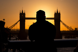 © Licensed to London News Pictures. 12/02/2018. London, UK. A man stops to take a photo of the sunrise over Tower Bridge in central London this morning, as temperatures in the capital dropped to freezing overnight. Photo credit : Tom Nicholson/LNP