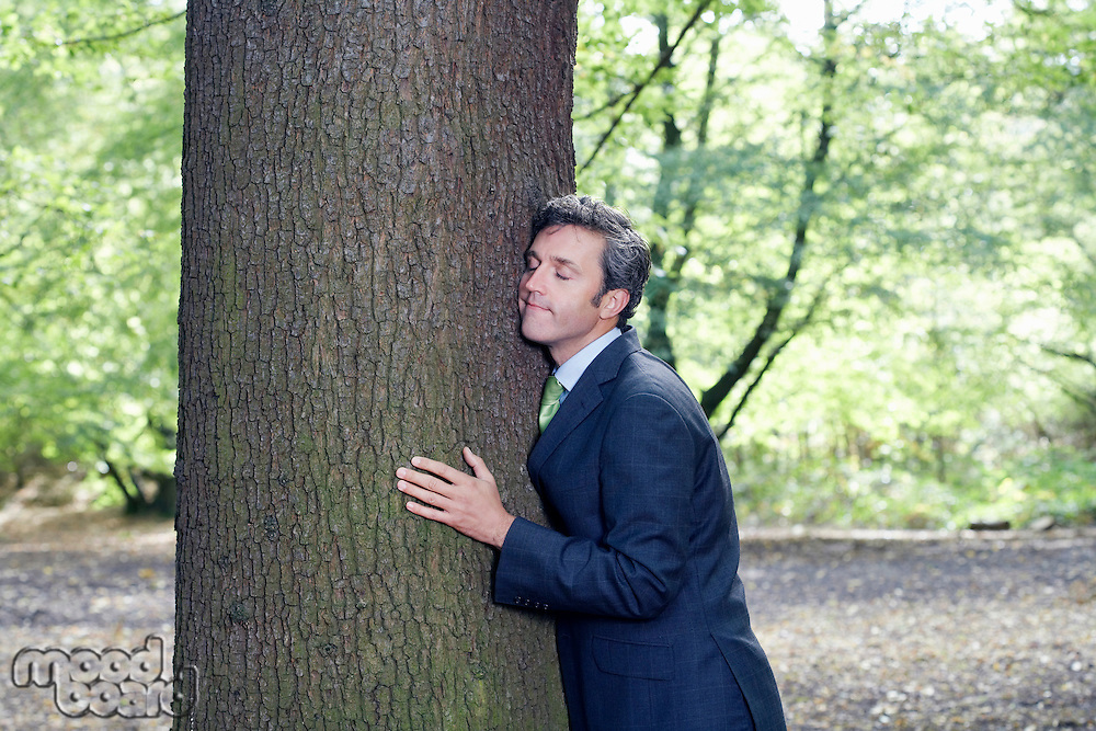 Mid adult business man hugging tree trunk eyes closed