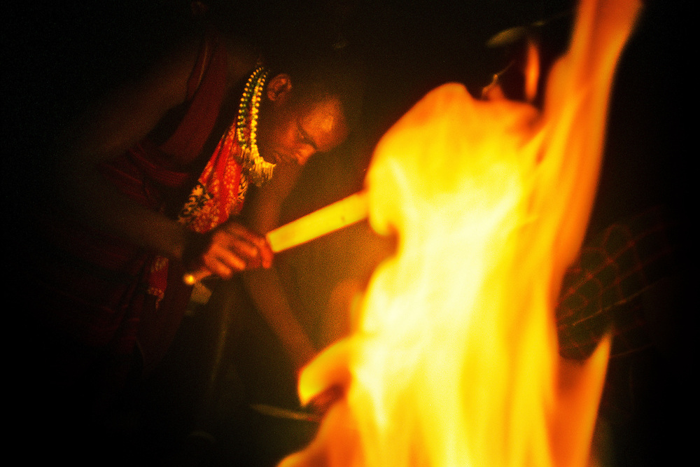 Tanzania, traditional Maasai life. Matayo cuts up some meat by the fire in Rondo, the temporary shelter which the warriors share with the cattle for the night.