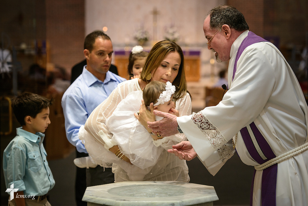 The Rev. Gary Schuschke, associate pastor, baptizes Londynn Levin as her mother Melissa Levin holds her at St. Luke's Lutheran Church on Sunday, March 6, 2016, in Oviedo, Fla. LCMS Communications/Erik M. Lunsford