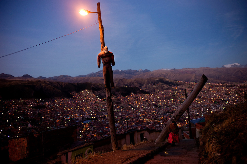 """A puppet hangs as a warning for thieves that they will be lynched and burnt if caught by neighbors, in El Alto, overlooking La Paz city, Bolivia. July, 18, 2010. With crime out of control neighbors in El Alto had decided to protect from thieves by themselves in what they call Justicia Comunitaria (community justice). Puppets are hanged around the city in organized neirghborhoods with signs that read """"caught thieves will be lynched and burnt alive"""", and so they do.  Every month mobs attack suspects and burn them alive immediately. In many cases innocent are killed by an uncontrolable mob. Amazingly there havent been any trial against these murder."""