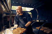 Texas Chocolate and BBQ Assistant Pit Master Brandon Allen loads briskets into Black October. Photographed September 28, 2018 in Tombal, TX for Texas Highways Magazine.<br /> <br /> Photographed by Houston,TX editorial photographer Nathan Lindstrom<br /> <br /> ©2018 Nathan Lindstrom