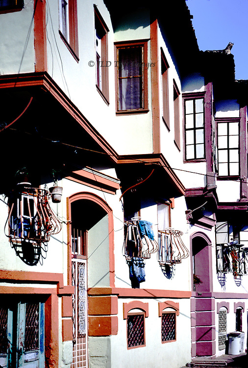 Row houses in Ayvalik, newly built on traditional design.  Angular projecting upper storeys, curved iron protective bars on lower windows, arched doorways colored orange and purple.