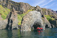 Tourists in a zodiac beneath a columnar basalt arch at Kuannersuit on the southside of Disko Island, Greenland.