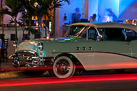 Antique Car Parked on Ocean Drive, Miami Beach Art Deco District at Night.