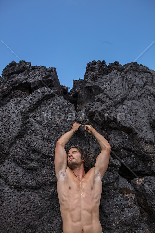 man without a shirt against volcanic rock