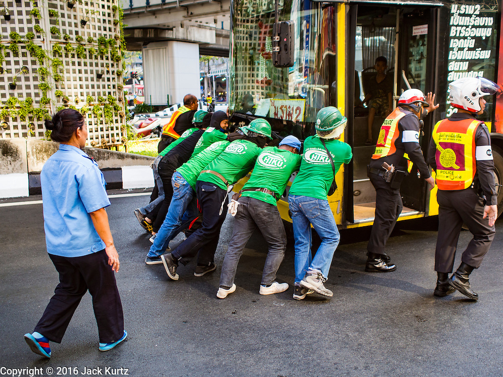 11 MAY 2016 - BANGKOK, THAILAND: Construction workers push a broken down bus out of traffic at the corner of Rama I and Phaya Thai Streets in central Bangkok. The bus was eastbound on Rama I when it broke down. The construction workers were renovating the Siam Discovery Mall, on the northeast corner of the intersection. The police went to the site and gathered the workers to push the bus.    PHOTO BY JACK KURTZ