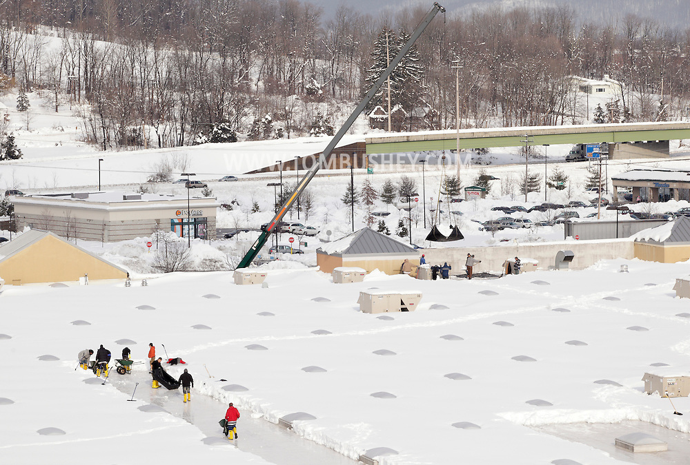 Harriman, New York - Workers in the foreground use shovels to remove snow from the roof of the Walmart store after a two-day storm dropped more than 30 inches of snow on Feb. 27, 2010. The crane in the background is lifting tarps full of snow off the roof. The store remained closed until the snow was removed and the roof was inspected.